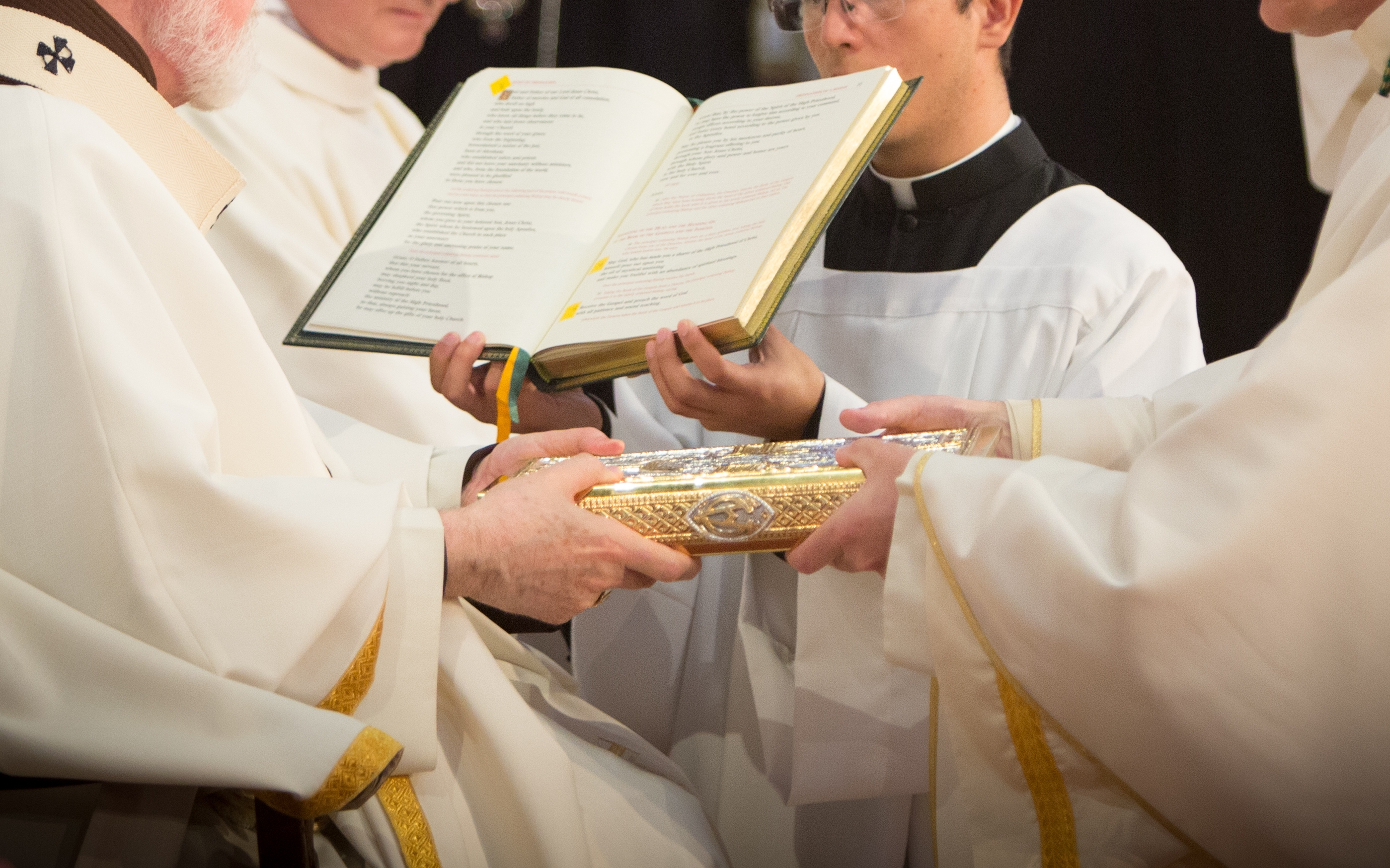 Screenshot of the principal consecrator handing a new bishop the Book of the Gospels